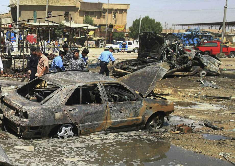 Iraqi security forces inspect the site of a car bomb in Basra, 340 miles southeast of Baghdad. A new wave of attacks are targeting Shiite-dominated cities. Photo: Nabil Al-Jurani / Associated Press