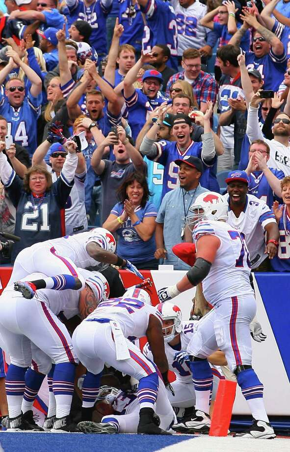 ORCHARD PARK, NY - SEPTEMBER 15:Fans celebrate as Buffalo Bills players pile on top of  Steve Johnson #13 of the Buffalo Bills after he caught the game winning touchdown against the Carolina Panthers at Ralph Wilson Stadium on September 15, 2013 in Orchard Park, New York.Buffalo won 24-23.  (Photo by Rick Stewart/Getty Images) ORG XMIT: 175878273 Photo: Rick Stewart / 2013 Getty Images