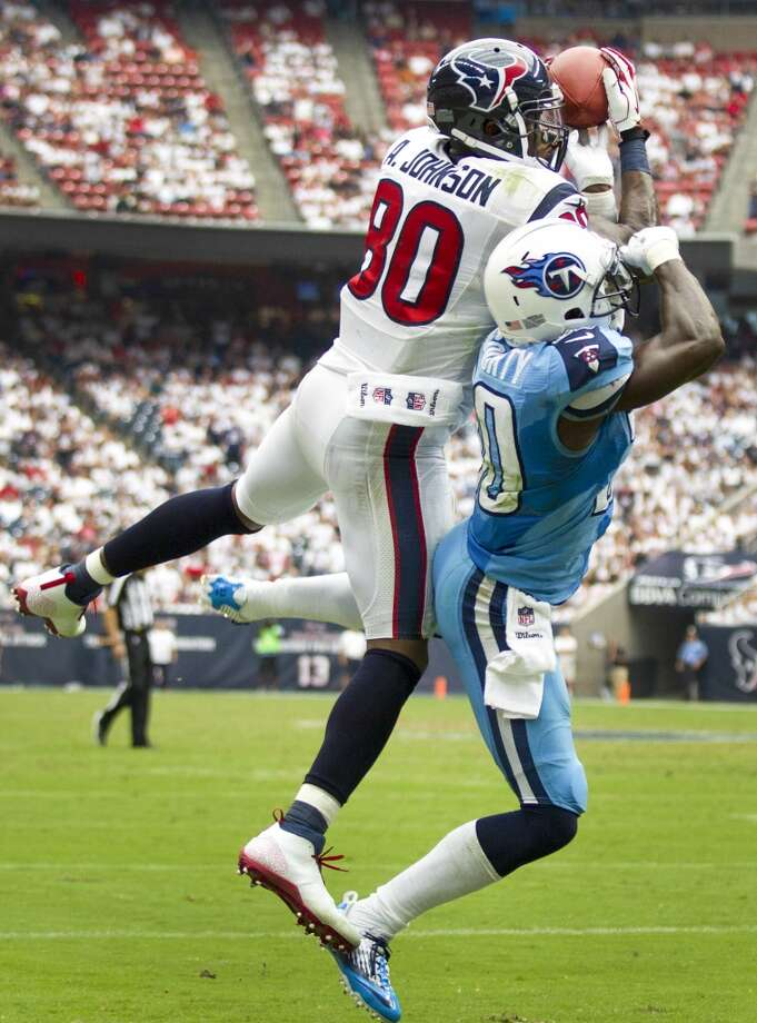 Texans wide receiver Andre Johnson leaps to make a catch over Titans cornerback Jason McCourty. Photo: Brett Coomer, Houston Chronicle