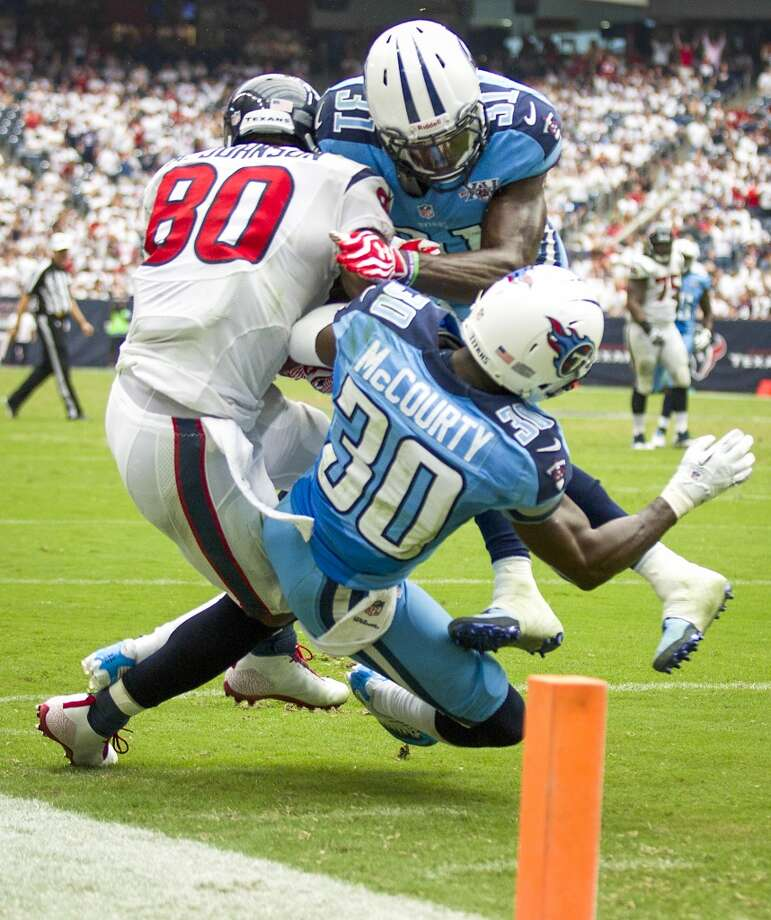 Texans wide receiver Andre Johnson s hit by Titans strong safety Bernard Pollard (31) and cornerback Jason McCourty (30) as he makes a catch near the goal line during the fourth quarter. Photo: Brett Coomer, Houston Chronicle