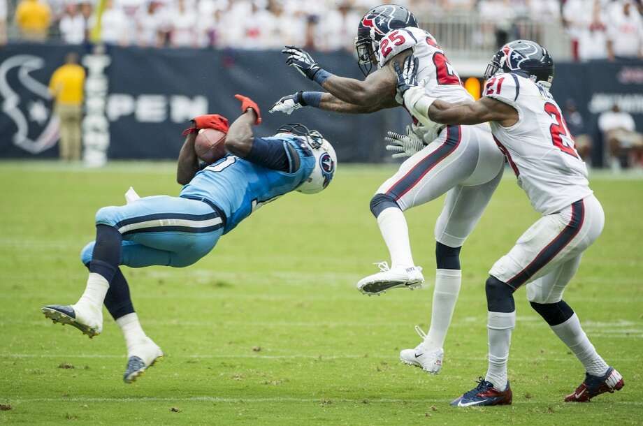 Titans wide receiver Kendall Wright is hit by Texans cornerback Kareem Jackson (25) as he makes a catch during the second half. Jackson was penalized for unnecessary roughness on play. Photo: Smiley N. Pool, Houston Chronicle