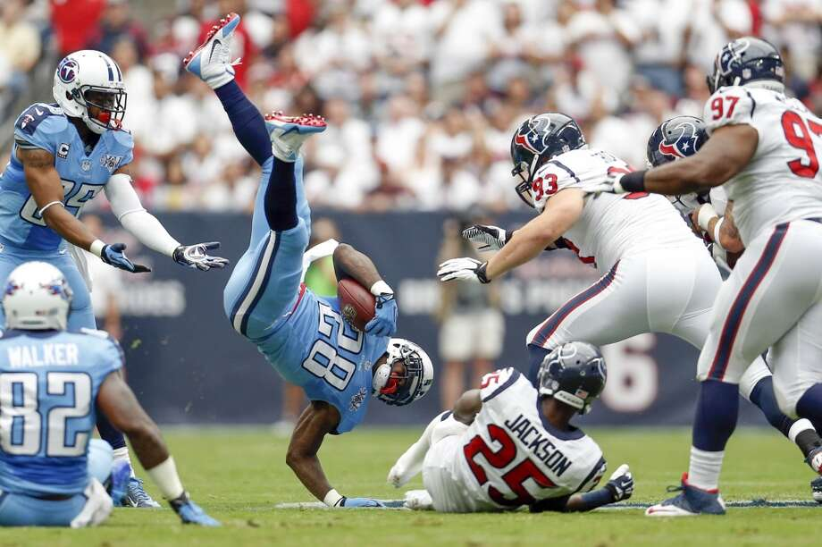 Titans running back Chris Johnson is upended by Texans cornerback Kareem Jackson during the first quarter. Photo: Karen Warren, Houston Chronicle