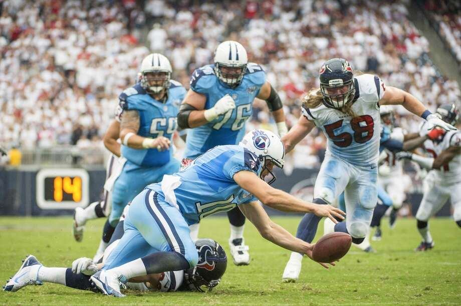 Titans quarterback Jake Locker chases a fumble with Texans defensive end J.J. Watt and linebacker Brooks Reed after having a snap sail over his head. Photo: Smiley N. Pool, Houston Chronicle
