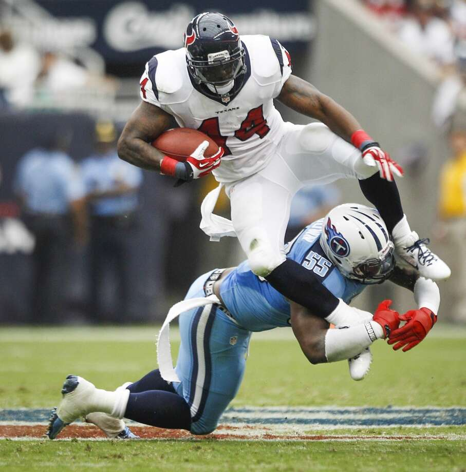 Texans running back Ben Tate is tripped up by Titans outside linebacker Zach Brown. Photo: Brett Coomer, Houston Chronicle