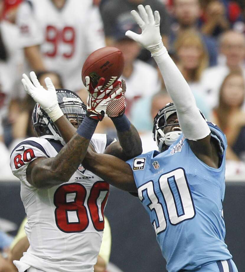 Titans cornerback Jason McCourty breaks up a pass intended for Texans wide receiver Andre Johnson. Photo: Brett Coomer, Houston Chronicle