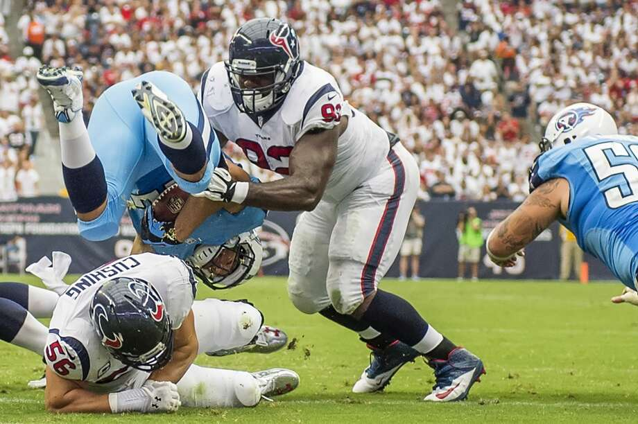 Titans running back Jackie Battle is upended by Texans inside linebacker Brian Cushing and defensive end Jared Crick. Photo: Smiley N. Pool, Houston Chronicle