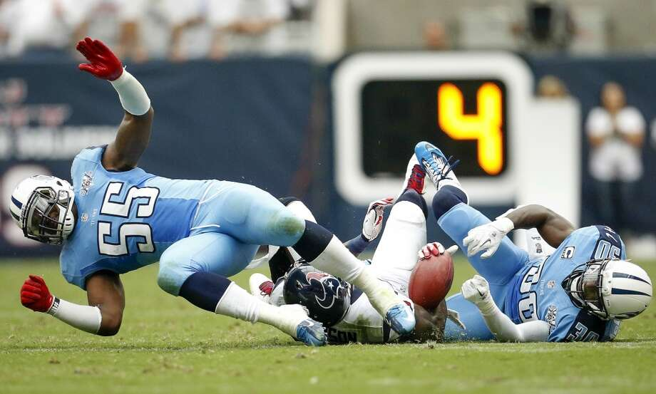 Texans wide receiver Andre Johnson is tackled by Titans linebacker Zach Brown (55) and cornerback Jason McCourty (30). Photo: Karen Warren, Houston Chronicle