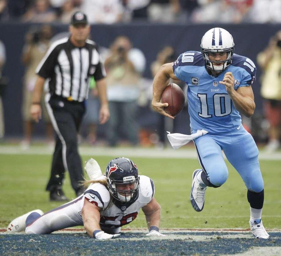 Titans quarterback Jake Locker scrambles away from Texans outside linebacker Brooks Reed. Photo: Brett Coomer, Houston Chronicle