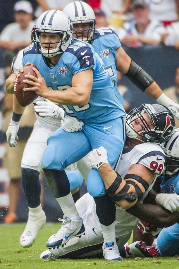 Texans defensive end J.J. Watt brings down Titans quarterback Jake Locker. Photo: Smiley N. Pool, Houston Chronicle