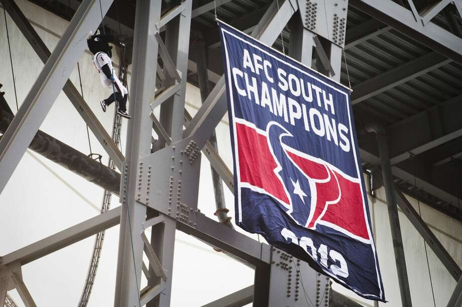 Texans mascot Toro rappels from the top of the stadium as the 2012 AFC South Champions banner is unfurled before the game. Photo: Houston Chronicle