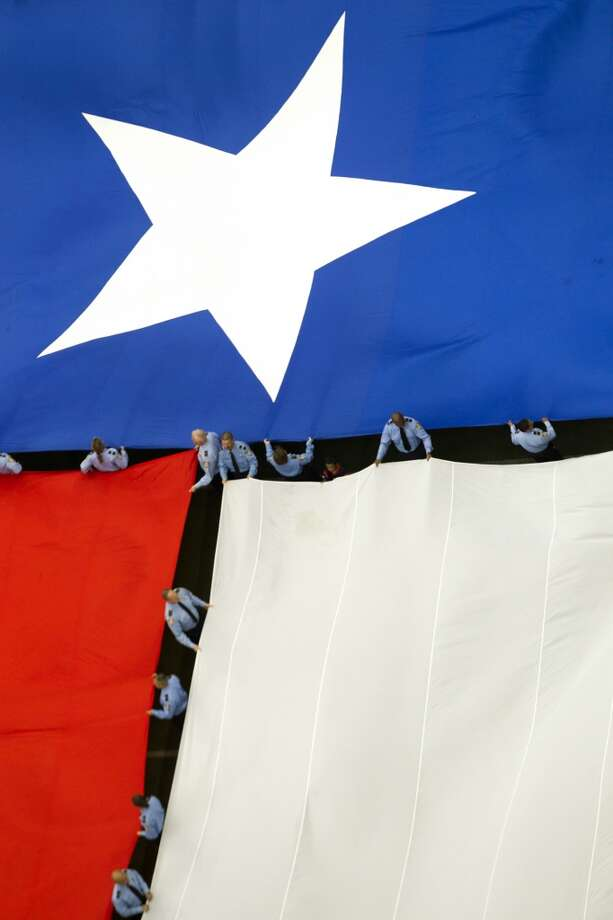 A Texas flag is held by firefighters before the Texans home opener against the Titans. Photo: Houston Chronicle