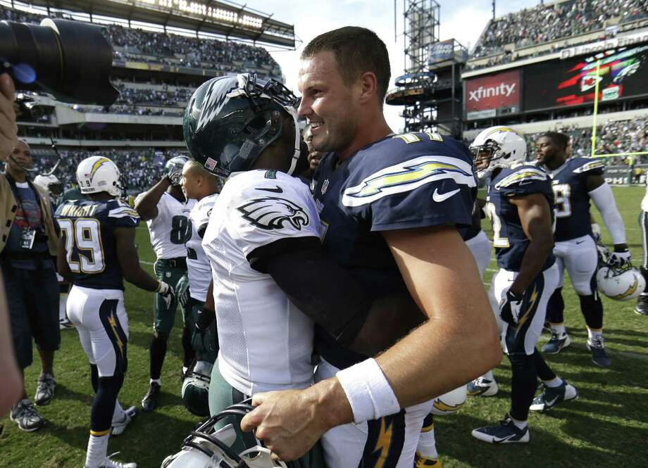 Eagles QB Michael Vick (left) shares a hug with Philip Rivers, his Chargers' counterpart, after their offenses produced a combined 1,150 yards. Photo: Matt Rourke / Associated Press