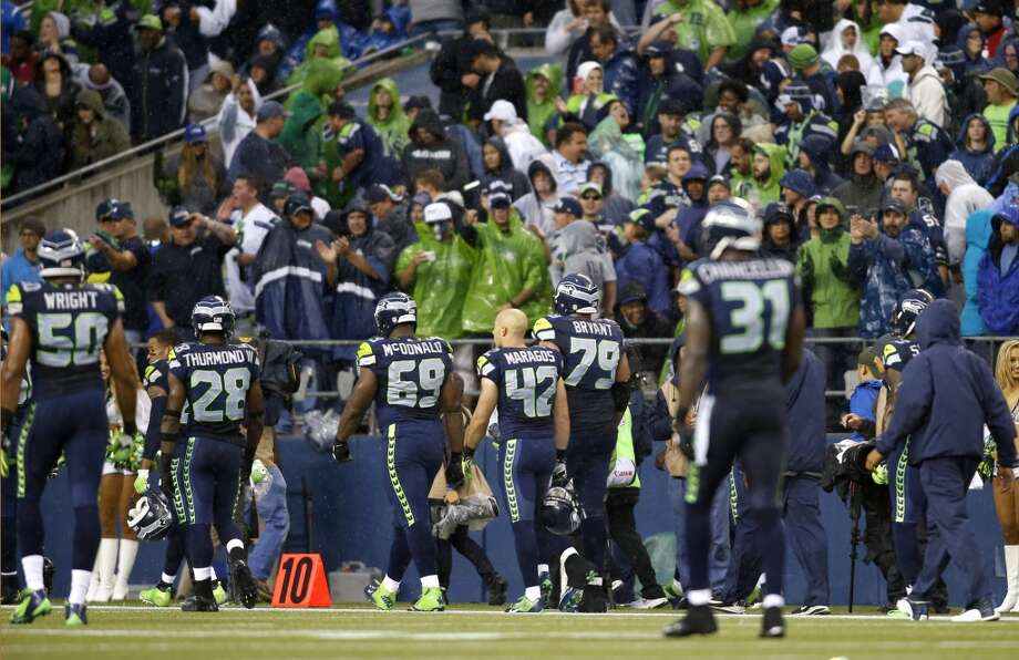 Seattle Seahawks football players walk off the field after a weather delay of their NFL football game against the San Francisco 49ers was called due to lightning in the area, Sunday, Sept. 15, 2013, in Seattle. (AP Photo/John Froschauer) Photo: John Froschauer, AP