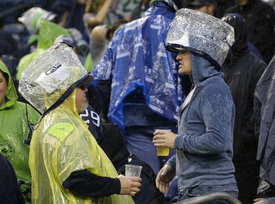 Seattle Seahawks fans wear official approved NFL security bags as rain covers during a severe weather delay in the first half of an NFL football game between the Seattle Seahawks and the San Francisco 49ers Sunday, Sept. 15, 2013, in Seattle. (AP Photo/Elaine Thompson) Photo: Elaine Thompson, AP
