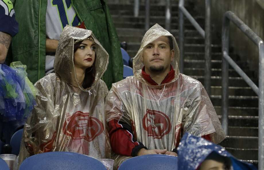 San Francisco 49ers fans wait out a severe weather delay in the first half of an NFL football game between the Seattle Seahawks and the San Francisco 49ers, Sunday, Sept. 15, 2013, in Seattle. (AP Photo/Elaine Thompson) Photo: Elaine Thompson, AP