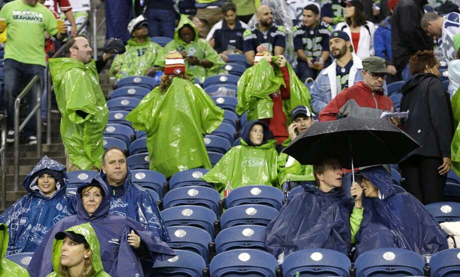 Fans wait out a severe weather delay in the first half of an NFL football game between the Seattle Seahawks and the San Francisco 49ers, Sunday, Sept. 15, 2013, in Seattle. (AP Photo/Elaine Thompson) Photo: Elaine Thompson, AP