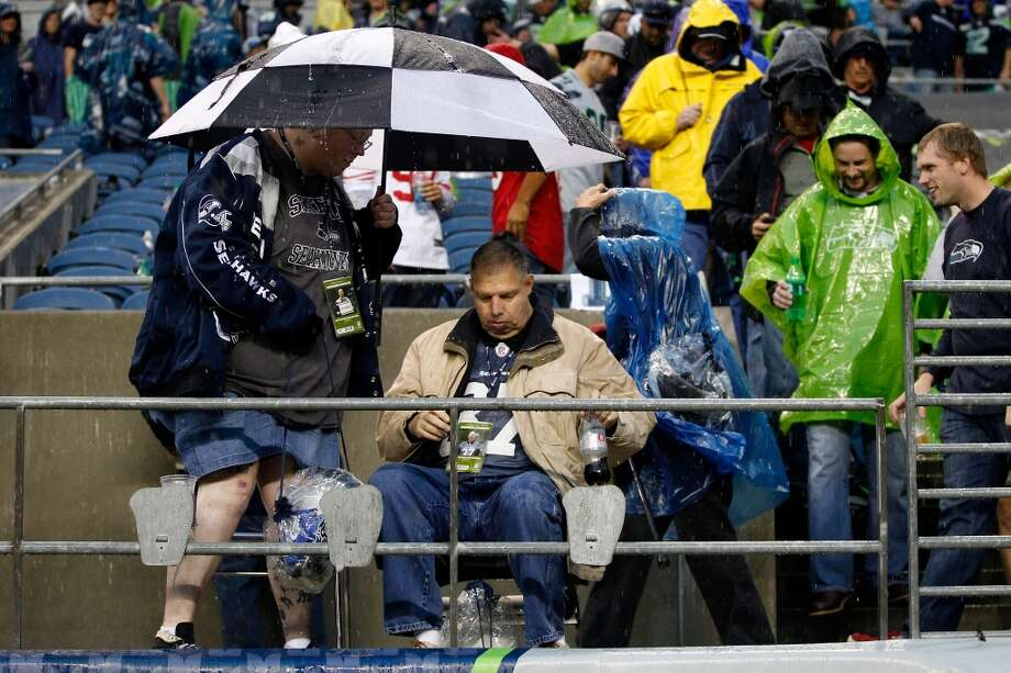 Fans use an umbrella as rain falls to delay the game between the San Francisco 49ers and the Seattle Seahawks at Qwest Field on September 15, 2013 in Seattle, Washington.  (Photo by Otto Greule Jr/Getty Images) Photo: Otto Greule Jr, Getty Images