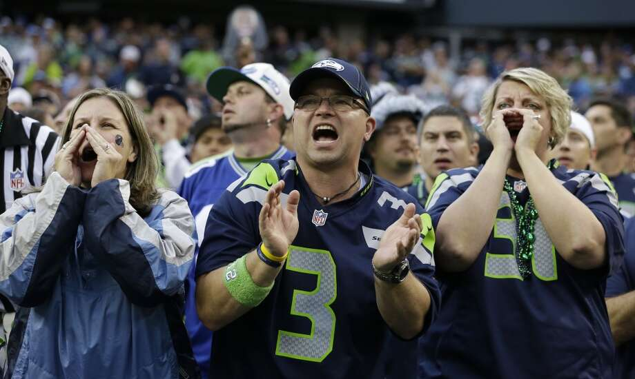 Seattle Seahawks fans yell during the first half of an NFL football game between the Seattle Seahawks and the San Francisco 49ers at CenturyLink Field, Sunday, Sept. 15, 2013, in Seattle. Fans were attempting to set a Guinness World Record for crowd noise at an athletic event during the game. (AP Photo/Elaine Thompson) Photo: Elaine Thompson, AP