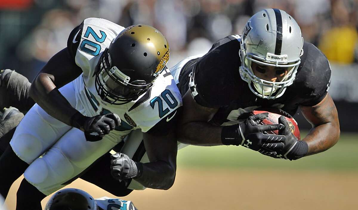 Mychal Rivera is hit by Jacksonville's Mike Harris after a run and catch in the fourth quarter. The Oakland Raiders played the Jacksonville Jaguars at O.co Coliseum in Oakland, Calif., on Sunday, September 15, 2013.