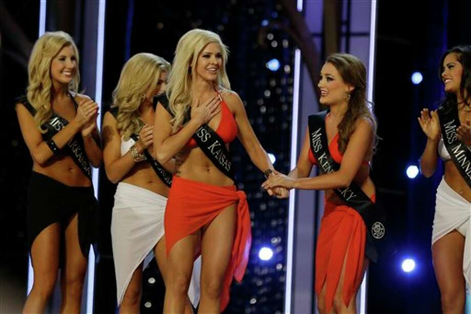 Miss Kansas Theresa Vail, left, reacts after advancing beyond the lifestyle competition as Miss Kentucky Jenna Day, right, holds her hand. Photo: Mel Evans, AP / AP