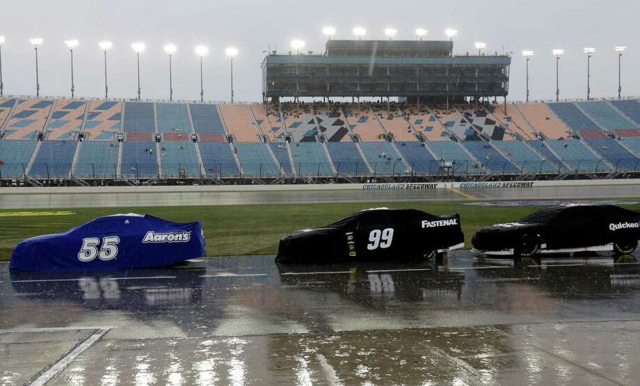 Covered Sprint Cup Series race cars are parked on pit road during rain delay in the NASCAR Sprint Cup series auto race at Chicagoland Speedway in Joliet, Ill., Sunday, Sept. 15, 2013. (AP Photo/Nam Y. Huh)  ORG XMIT: ILNH144 Photo: Nam Y. Huh / AP