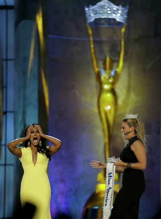 Miss New York Nina Davuluri, left, reacts after winning the Miss America 2014 pageant as Miss America 2013 Mallory Hagan approaches her. Photo: Julio Cortez, AP / AP