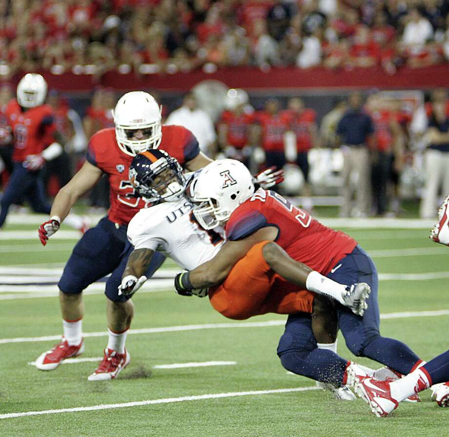 UTSA receiver Kam Jones is flattened by Arizona's Sione Tuihalamaka during the Wildcats' 38-13 victory Saturday. Photo: Wily Low / Associated Press