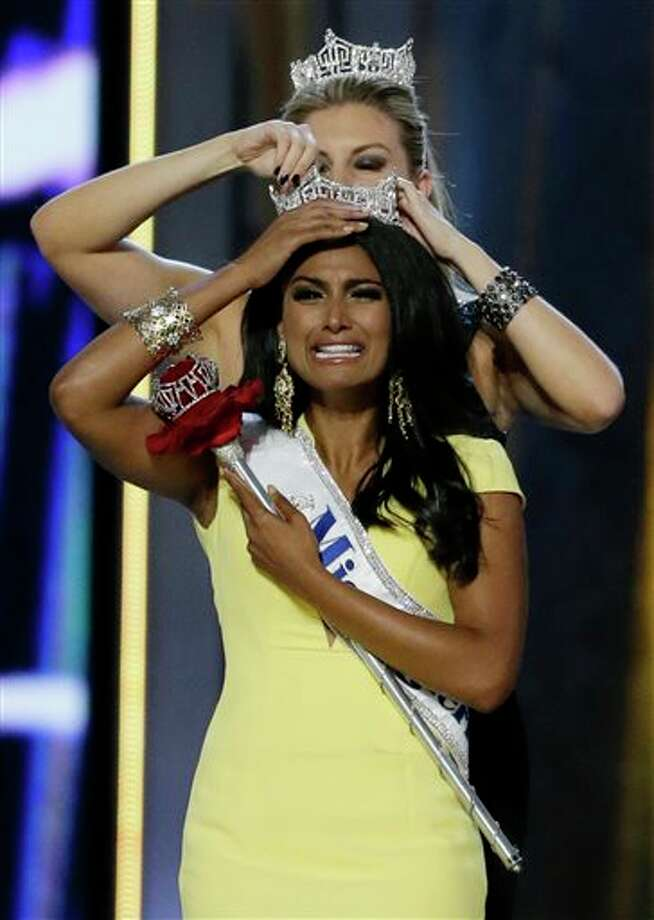 Miss New York Nina Davuluri, front, is crowned as Miss America 2014 by Miss America 2013 Mallory Hagan, Sunday, Sept. 15, 2013, in Atlantic City, N.J. Photo: Julio Cortez, AP / AP