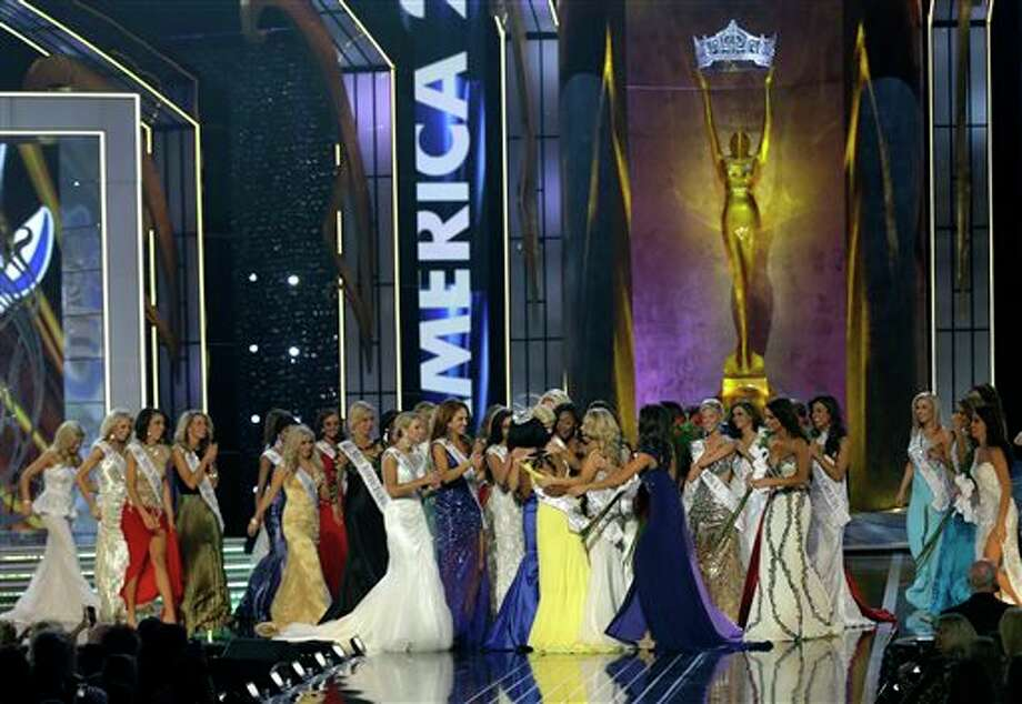 Miss New York Nina Davuluri, center left in yellow, is approached by contestants after Davuluri was crowned as Miss America 2014. Photo: Mel Evans, AP / AP