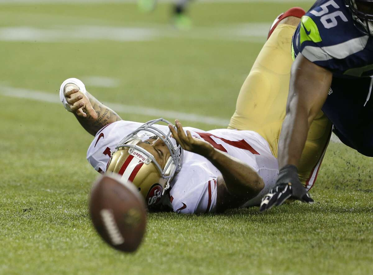 San Francisco 49ers quarterback Colin Kaepernick lies on the turf after fumbling the football in the first half of an NFL football game against the Seattle Seahawks, Sunday, Sept. 15, 2013, in Seattle. (AP Photo/Elaine Thompson)