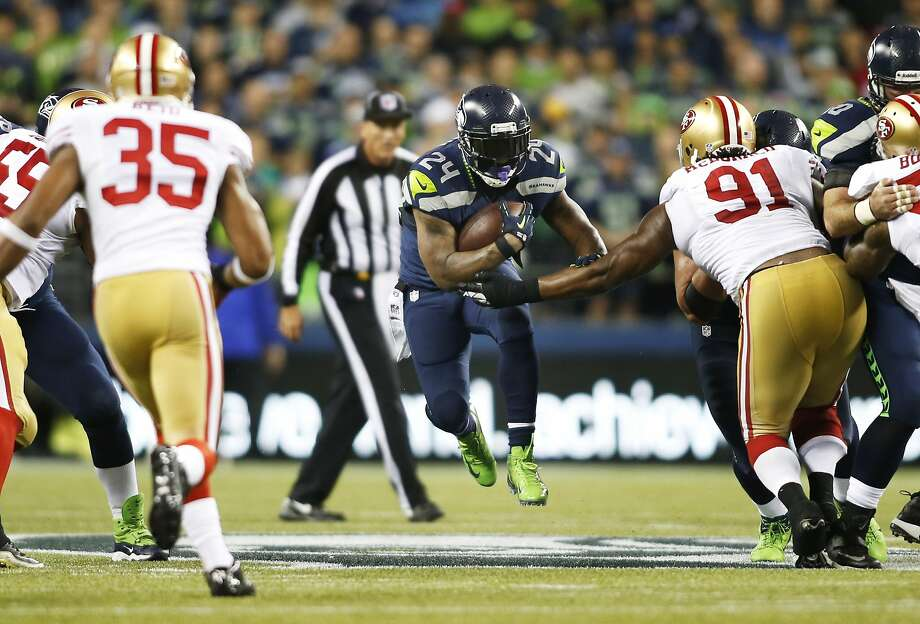Seattle Seahawks' running back Marshawn Lynch (24) leaps as he carries the ball against San Francisco 49ers' Eric Reid (35) and Ray McDonald (91) in the first half of an NFL football game, Sunday, Sept. 15, 2013, in Seattle. (AP Photo/John Froschauer) Photo: John Froschauer, Associated Press