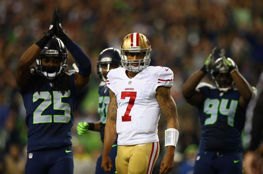 Colin Kaepernick of the San Francisco 49ers looks on as Richard Sherman #25 and D'Anthony Smith #94 of the Seattle Seahawks celebrate a safety during their game at Qwest Field on September 15, 2013 in Seattle, Washington. Photo: Jonathan Ferrey, Getty Images