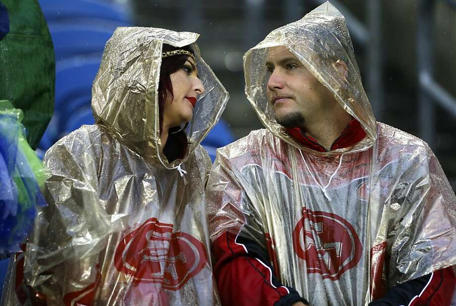 San Francisco 49ers fans wait out a severe weather delay in the first half of an NFL football game between the Seattle Seahawks and the San Francisco 49ers, Sunday, Sept. 15, 2013, in Seattle. (AP Photo/Elaine Thompson) Photo: Elaine Thompson, Associated Press