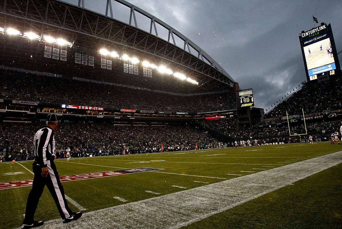 SEATTLE, WA - SEPTEMBER 15: Side judge Joe Larrew #73 walks the sideline as rain falls to delay the game between the San Francisco 49ers and the Seattle Seahawks at Qwest Field on September 15, 2013 in Seattle, Washington. (Photo by Jonathan Ferrey/Getty Images)