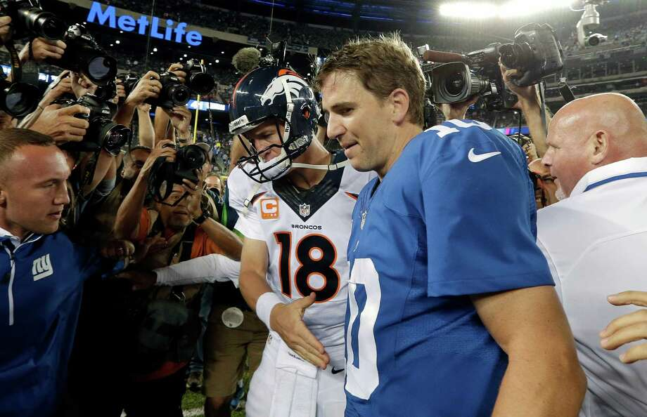 Denver Broncos quarterback Peyton Manning (18) shakes hands with his brother New York Giants' quarterback Eli Manning (10) after an NFL football game Sunday, Sept. 15, 2013, in East Rutherford, N.J. The Broncos won the game 41-23. (AP Photo/Frank Franklin II) ORG XMIT: ERU129 Photo: Frank Franklin II / AP