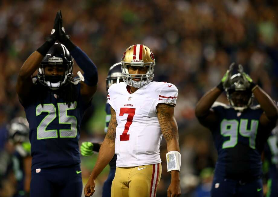 Colin Kaepernick looks on as Richard Sherman and D'Anthony Smith (#94) of the Seattle Seahawks celebrate a safety in the second quarter. Photo: Jonathan Ferrey, Getty Images