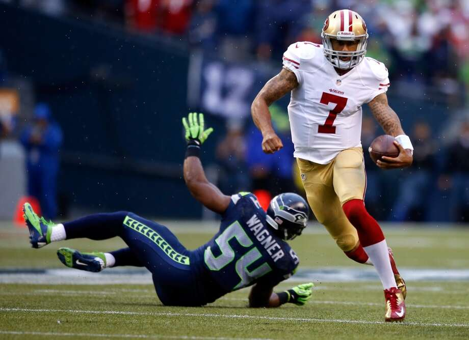 Colin Kaepernick runs the ball against Bobby Wagner of the Seattle Seahawks during the first quarter. Photo: Otto Greule Jr, Getty Images