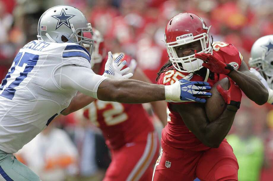 Chiefs running back Jamaal Charles, who had 55 yards on the ground, avoids the Cowboys' Jason Hatcher in the first half. Photo: Charlie Riedel / Associated Press