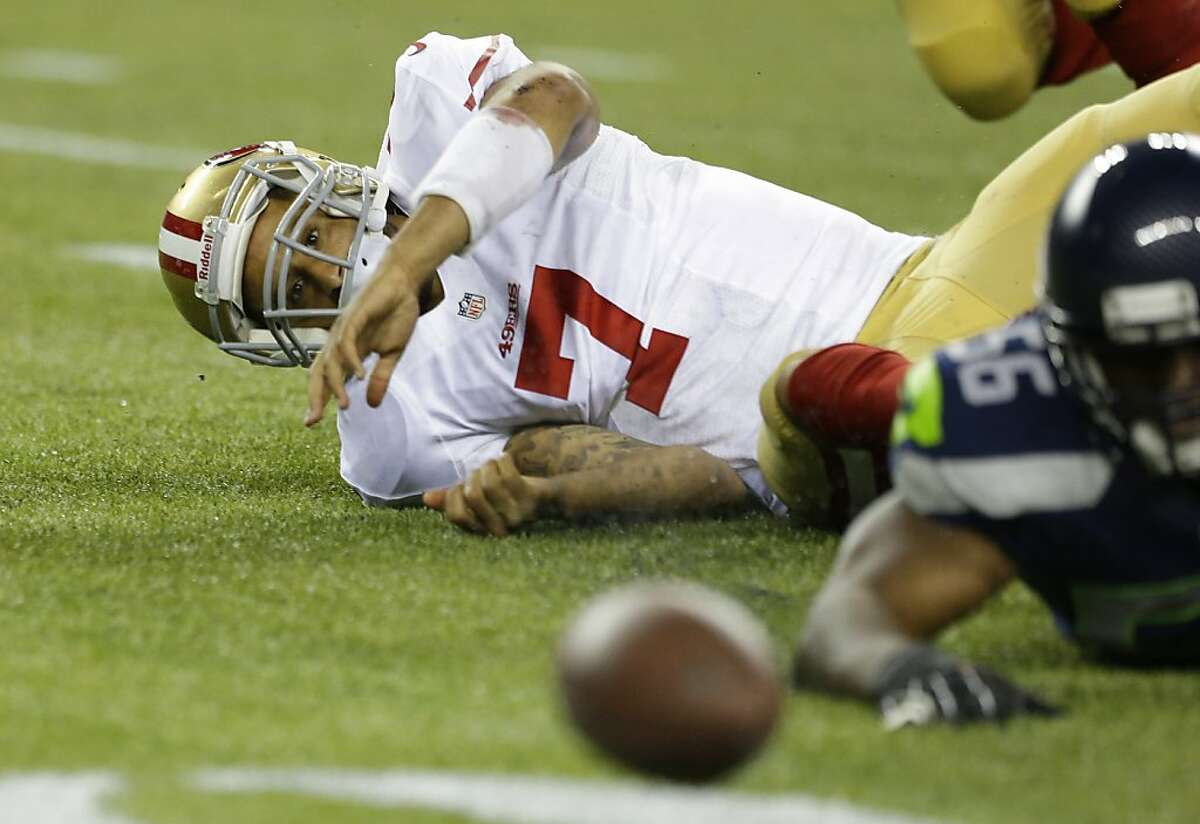 Colin Kaepernick is helpless to prevent a turnover after he was sacked by Seattle's Cliff Avril, a hit that produced a fumble.