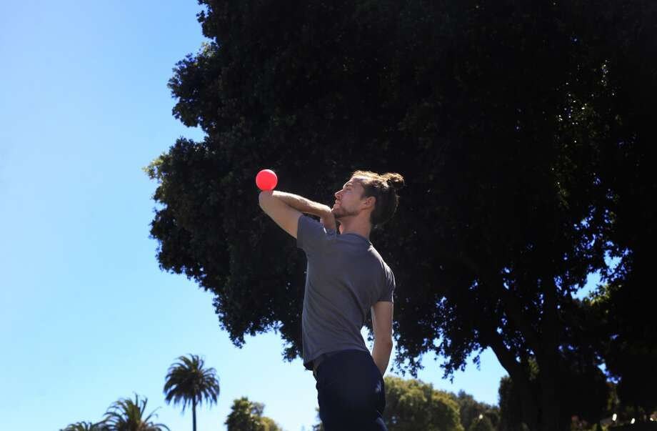 Balancing a ball on the outside of his elbow, professional contact juggler Richard Hartnell practices his technique in Dolores Park in San Francisco, Calif. Photo: The Chronicle