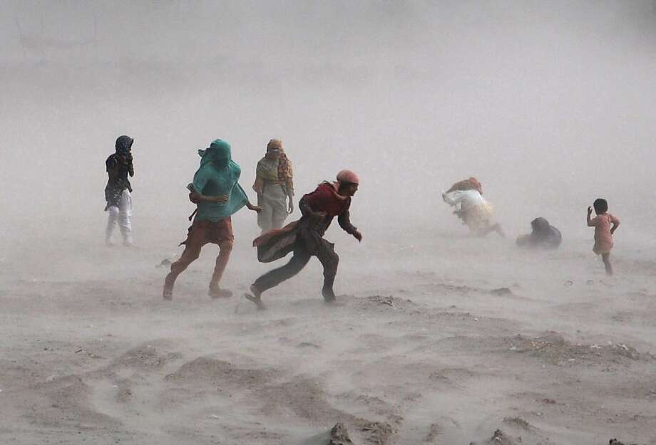 Fierce winds buffet pedestrians near the Ravi River in Lahore, Pakistan. Photo: Arif Ali, AFP/Getty Images