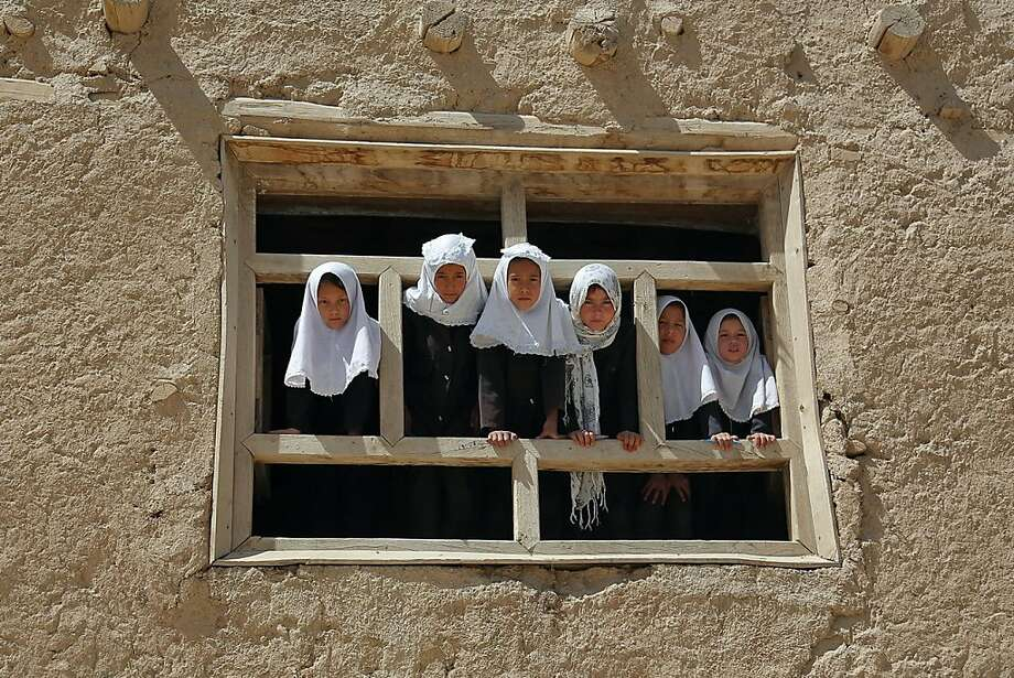 Window watchers: Afghan schoolgirls check out what's going on outside their school in Ghazni. Photo: Rahmatullah Alizada, AFP/Getty Images