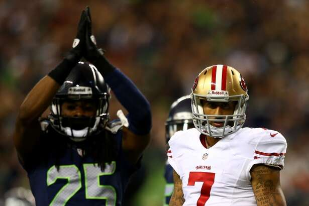 SEATTLE, WA - SEPTEMBER 15:   Colin Kaepernick #7 of the San Francisco 49ers looks on as Richard Sherman #25 and D'Anthony Smith #94 of the Seattle Seahawks celebrate a saftey during their game at Qwest Field on September 15, 2013 in Seattle, Washington.  (Photo by Jonathan Ferrey/Getty Images)