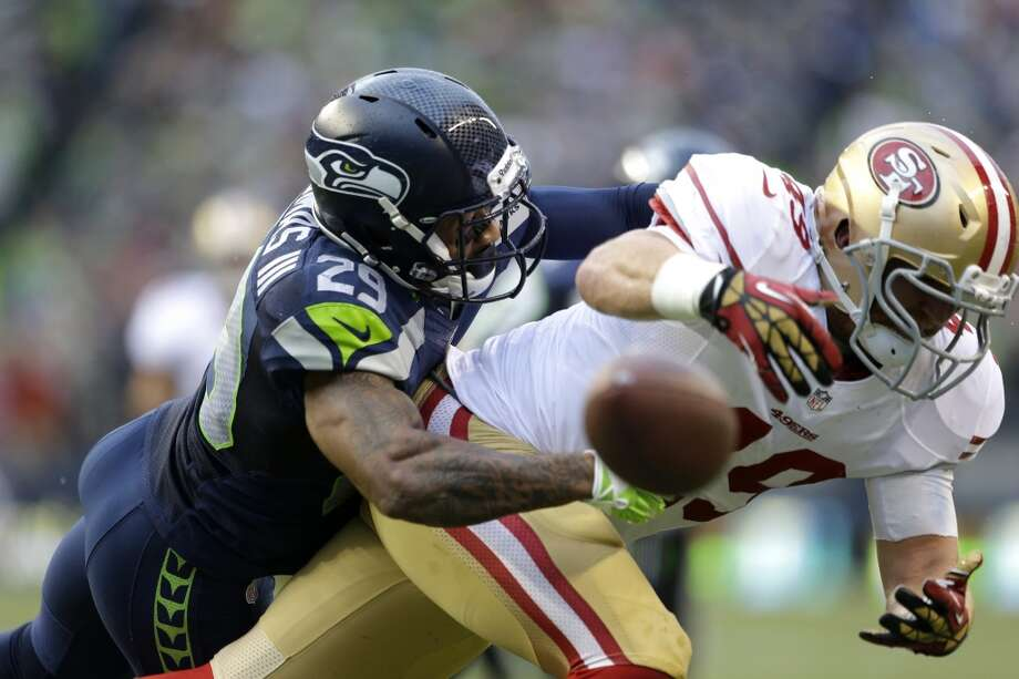San Francisco 49ers' Bruce Miller, right, misses a catch as Seattle Seahawks' Earl Thomas defends in the first half of an NFL football game, Sunday, Sept. 15, 2013, in Seattle. (AP Photo/Elaine Thompson) Photo: AP