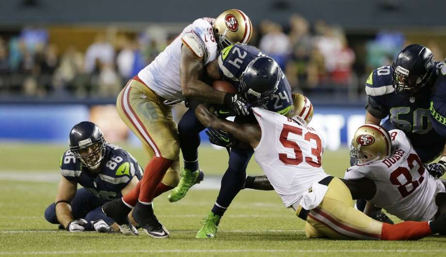 Seattle Seahawks' Marshawn Lynch, center, is brought down by San Francisco 49ers Ahmad Brooks, left, and NaVorro Bowman in the second half of an NFL football game, Sunday, Sept. 15, 2013, in Seattle. (AP Photo/Elaine Thompson) Photo: AP