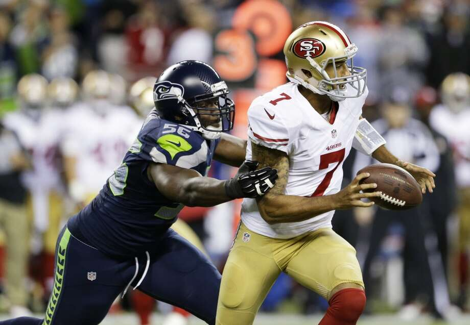 Seattle Seahawks' Cliff Avril, left, forces a fumble by San Francisco 49ers quarterback Colin Kaepernick in the first half of an NFL football game, Sunday, Sept. 15, 2013, in Seattle. The Seahawks recovered the ball on the play. (AP Photo/Elaine Thompson) Photo: AP