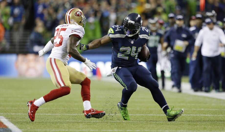 Seattle Seahawks running back Marshawn Lynch (24) runs the ball as San Francisco 49ers cornerback Tarell Brown, left, closes in during the first half of an NFL football game, Sunday, Sept. 15, 2013, in Seattle. (AP Photo/Elaine Thompson) Photo: ASSOCIATED PRESS
