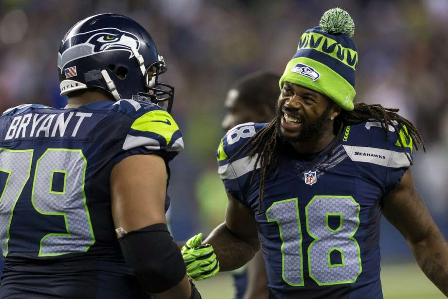 Sidney Rice, right, jokes with teammates during the second half of the home opener. Photo: JORDAN STEAD, SEATTLEPI.COM