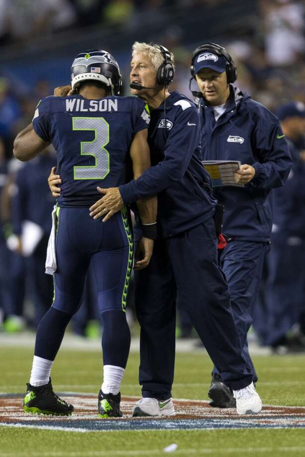 Head coach Pete Carroll, center, embraces quarterback Russell Wilson, left, during the second half. Photo: JORDAN STEAD, SEATTLEPI.COM
