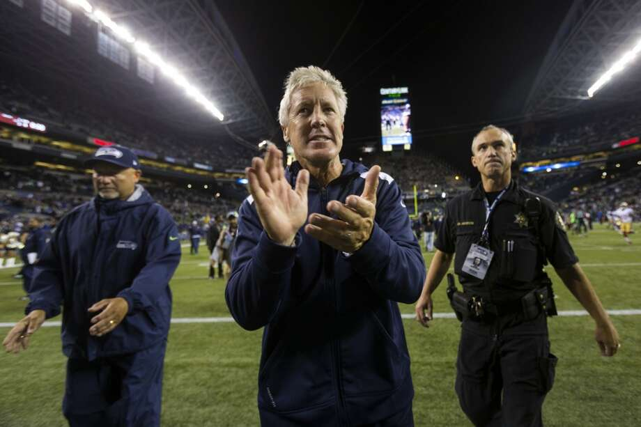 Head coach Pete Carroll, center, claps while walking off of the field. Photo: JORDAN STEAD, SEATTLEPI.COM